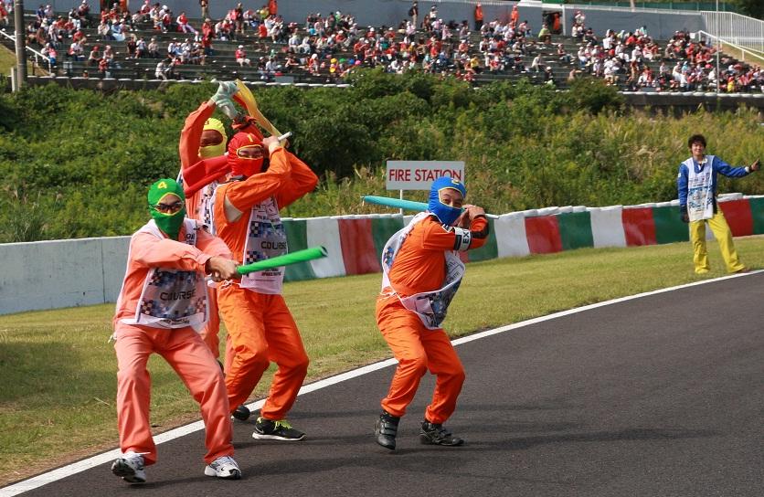 маршалы Сузуки размахивают флагами на Гран-при Японии 2012