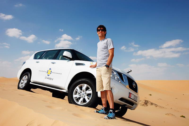 Марк Уэббер на фоне внедорожника Nissan в песчаной пустыне перед Гран-при Абу-Даби 2011