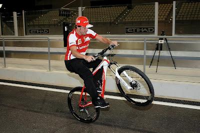 Фернандо Алонсо едет на заднем колесе на велосипеде на Гран-при Абу-Даби 2013