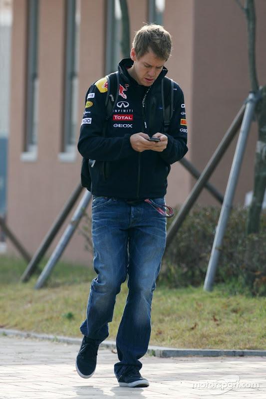 Себастьян Феттель пишет что-то на своем телефоне на Гран-при Кореи 2011