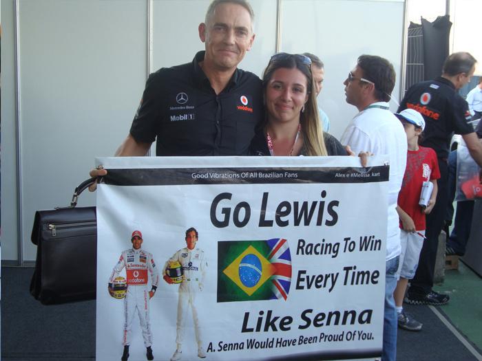 болельщица Melissa Kart фотографируется с Мартином Уитмаршом с баннером в поддержку пилота на Гран-при Бразилии 2011