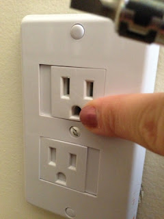 You can slide the plate on the front of the outlet cover to the right to plug something in.