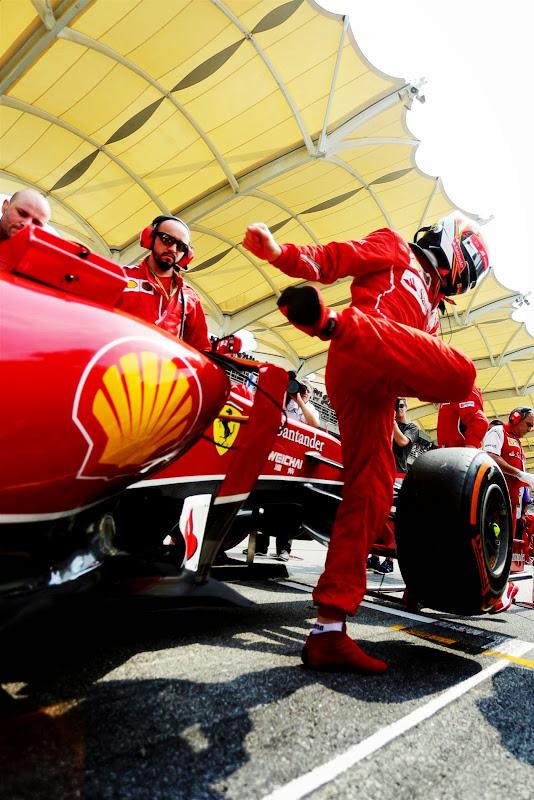 Кими Райкконен вылазит из болида Ferrari на стартовой решетке Куала-Лумпура на Гран-при Малайзии 2014