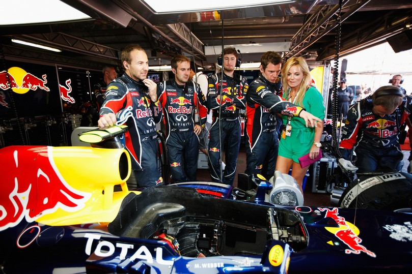 Джерри Холливел в боксах команды Red Bull изучает болид Формулы-1 с механиками перед гонкой на Гран-при Монако 2011