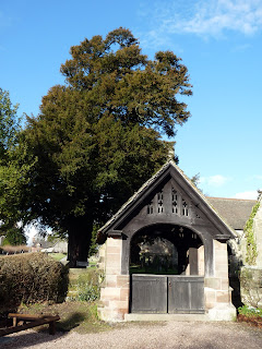 The lych gate to Ellastone Church. A lych gate was a roofed gate to a churchyard under which a bier is set down during a burial service to await the coming of the clergymen.