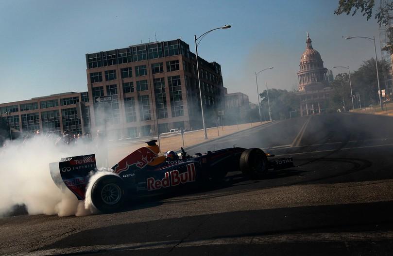 Дэвид Култхард жжет резину на своем Red Bull на фоне Texas Capitol