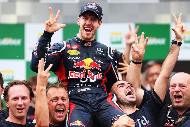 Себастьян Феттель на руках механиков Red Bull на подиуме Интерлагоса радуются победе в чемпионате на Гран-при Бразилии 2012