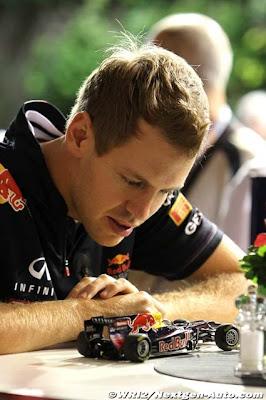 Себастьян Феттель и моделька Red Bull на Гран-при Сингапура 2011