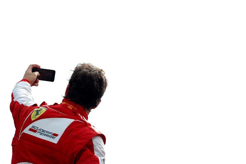 Фернандо Алонсо фотографирует себя на фоне болельщиков Монцы на подиуме Гран-при Италии 2013