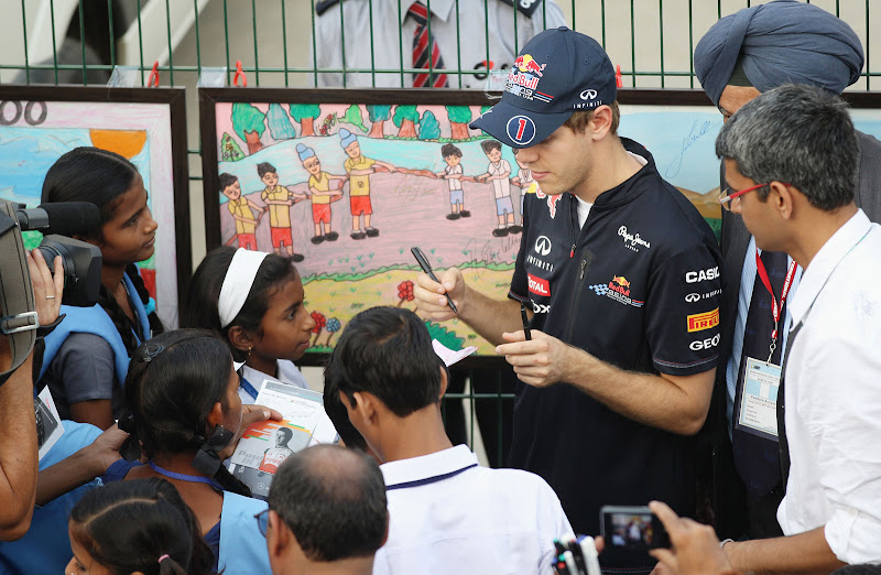 Себастьян Буэми раздает автографы индийским детям на Гран-при Индии 2011