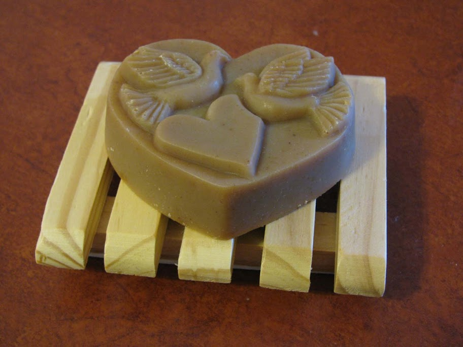 A Molded Heart of our Goat's Milk Soap on a Wooden Soap Dish