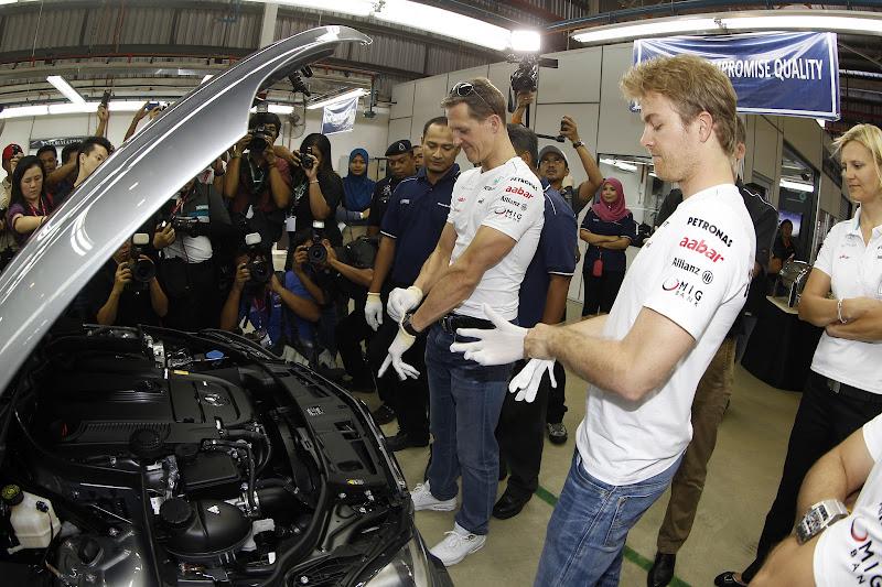 Михаэль Шумахер и Нико Росберг одевают белые перчатки на сборке Mercedes в Куала-Лумпур перед Гран-при Малайзии 2012