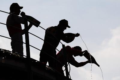 темные силуэты Дженсона Баттона, Себастьяна Феттеля и Фернандо Алонсо с шампанским на подиуме Монцы на Гран-при Италии 2011