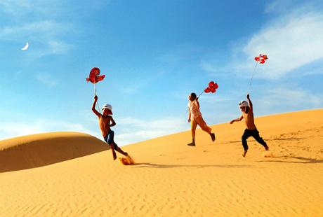 Ảnh trẻ em thả diều trên bãi cát vàng