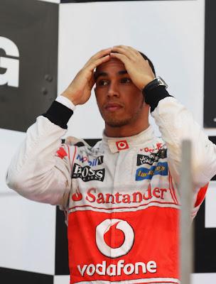 Льюис Хэмилтон держится за голову на подиуме Йонама на Гран-при Кореи 2011