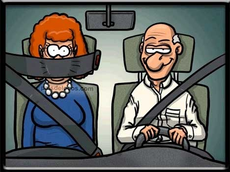 A man driving a car while a woman sits beside him, with her seatbelt across her mouth, preventing her from commenting.