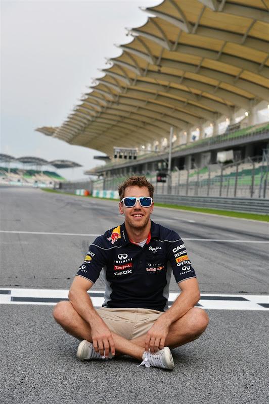 Себастьян Феттель в солнцезащитных очках на старт-финишной черте трассы Куала-Лумпур на Гран-при Малайзии 2013