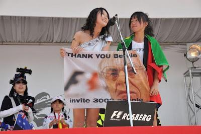 болельщицы на сцене с плакатом Берни Экклстоуна на Гран-при Японии 2011