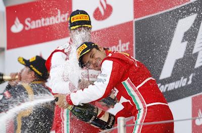 Кими Райкконен пьет шампанское, пока Фернандо Алонсо и Фелипе Масса разбрызгивают его на подиуме Гран-при Испании 2013