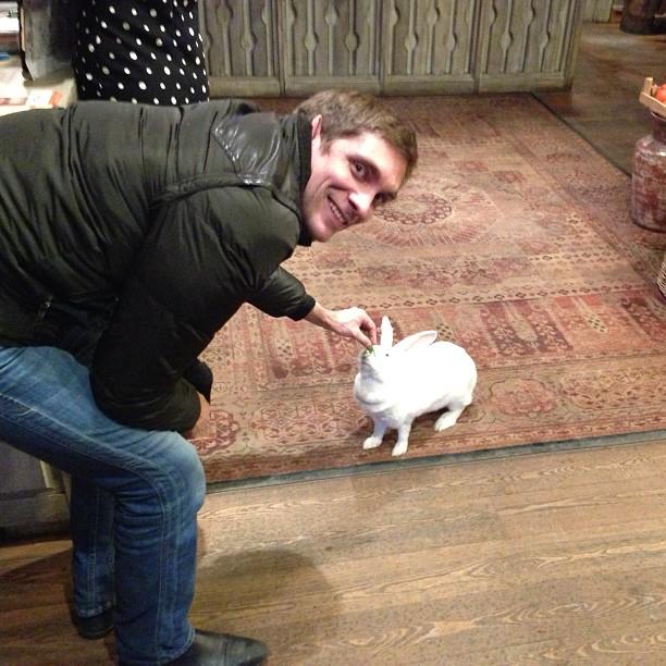 Виталий Петров кормит белого кролика