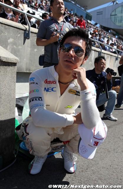 Камуи Кобаяши сидит на корточках на Гран-при Японии 2011