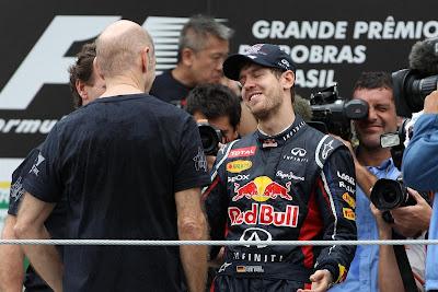Себастьян Феттель отмечает победу в чемпионате вместе с Эдрианом Ньюи и Кристианом Хорнером на подиуме Интерлагоса на Гран-при Бразилии 2012