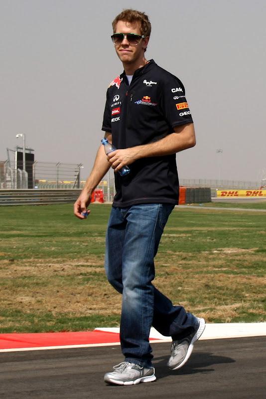 Себастьян Феттель с забавным лицом идет по трассе Буддх на Гран-при Индии 2011