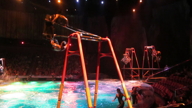 Performers diving off swings into the pool below.