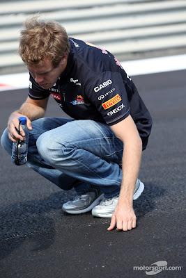 Себастьян Феттель рассматривает асфальт во время прогулки по треку перед Гран-при Абу-Даби 2011