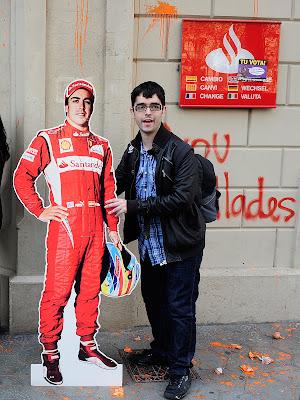 студент с фигурой Фернандо Алонсо на фоне испанского банка Santander в Барселоне 21 ноября 2011