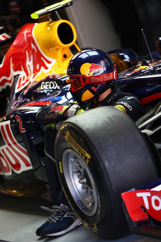механик Red Bull сидит рядом с болидом в гараже на предсезонных тестах 2012 в Барселоне