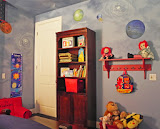 Gabriel's Bedroom - 2 of 6 - A bookcase holds favorite books and treasures. A shelf with hooks below holds his backpack and other toys.