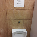 """Worst, smelliest, hottest dressing room in a while...the sign says """"Please Flush! It will help keep the flies away."""""""