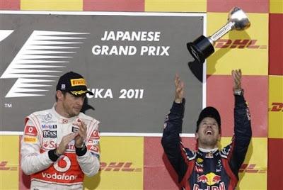 Себастьян Феттель подбрасывает свой трофей на подиуме Гран-при Японии 2011 - Дженсон Баттон аплодирует