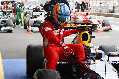 Фернандо Алонсо смотрит в направлении зеркала болида Red Bull Марка Уэббера на Гран-при Германии 2011
