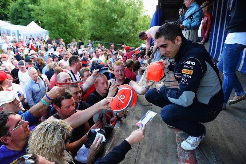Себастьян Буэми ставит автографы на кепках McLaren на Гран-при Великобритании 2013 в Сильверстоуне