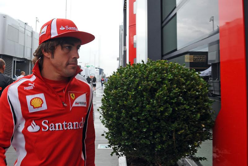 Фернандо Алонсо проходит мимо зеленого куста у паддока Ferrari на Гран-при Венгрии 2011