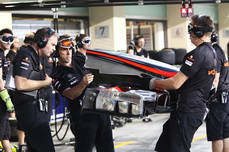 механики McLaren удивленно смотрят в передние антикрыло на Гран-при Абу-Даби 2011