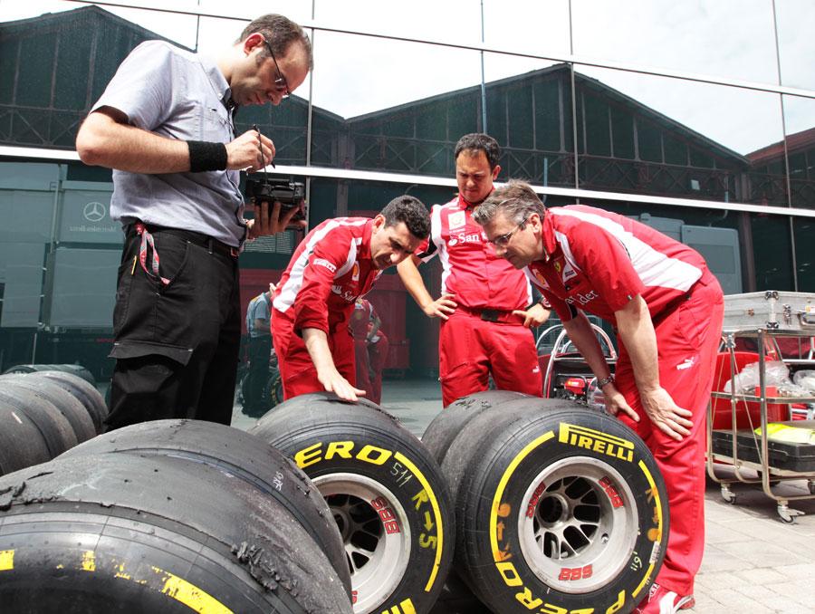 Андреа Стелла и механики Ferrari смотрят резину Pirelli на Гран-при Европы 2011