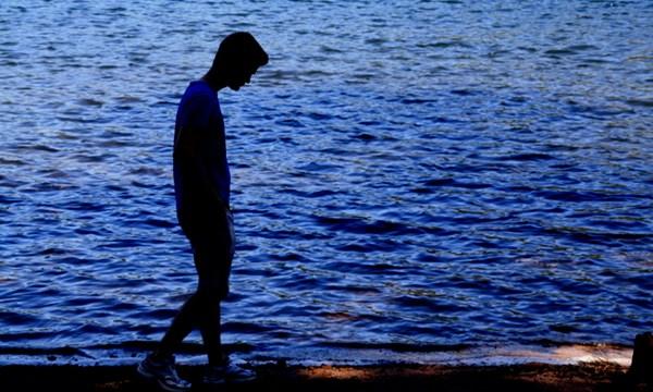 Ảnh con trai buồn đi dạo quanh biển