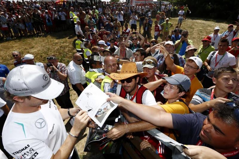 Нико Росберг раздает автографы на трибуне с болельщиками на Гран-при Венгрии 2013