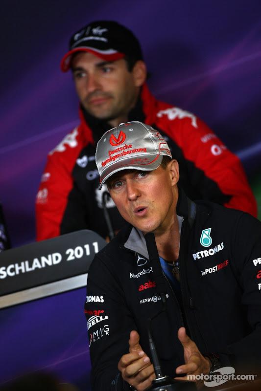Михаэль Шумахер что-то объясняет и Тимо Глок позади на пресс-конференции Нюрбургринга на Гран-при Германии 2011