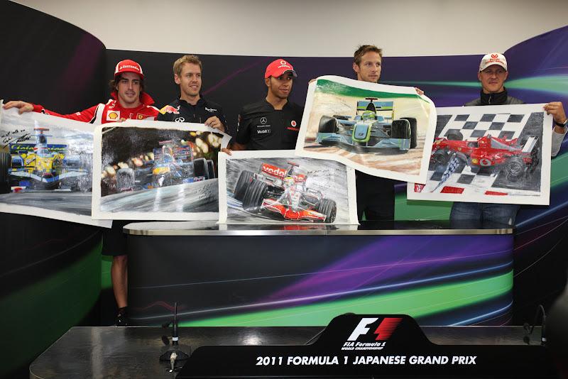 пилоты держат постеры болидов на Гран-при Японии 2011