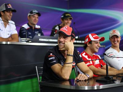 улыбающийся Дженсон Баттон отворачивается на пресс-конференции в четверг на Гран-при Бразилии 2011