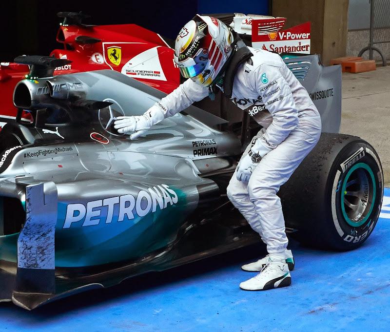 Льюис Хэмилтон загибается перед своим Mercedes после победы на Гран-при Китая 2014