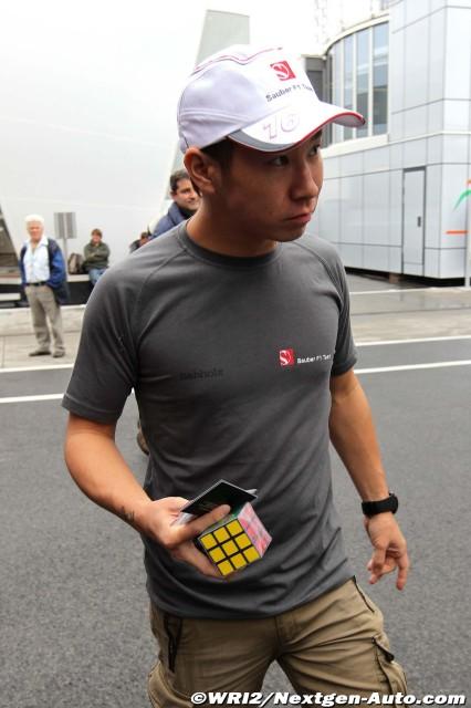 Камуи Кобаяши идет по паддоку Хунгароринга с Кубиком Рубиком в руках на Гран-при Венгрии 2011