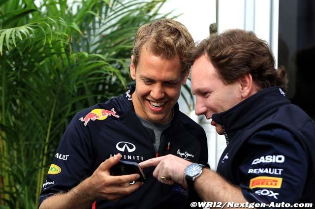 Себастьян Феттель показывает что-то Кристиану Хорнеру на своем телефоне на Гран-при Канады 2012