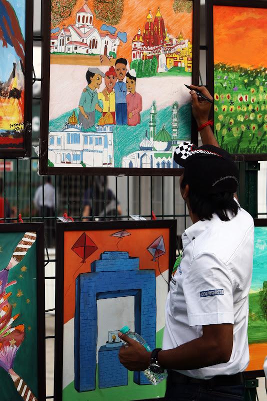 Нараин Картикеян ставит автограф на рисунках индийских школьников на Гран-при Индии 2011