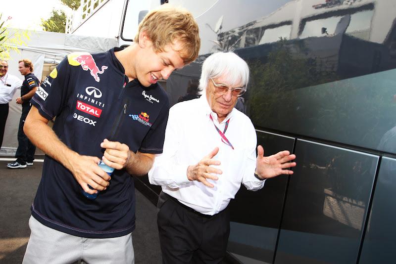 Берни Экклстоун показывает на руках что-то Себастьяну Феттелю на Гран-при Италии 2011