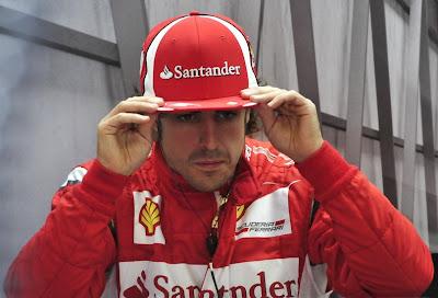 Фернандо Алонсо поправляет кепку в боксах на Гран-при Венгрии 2011